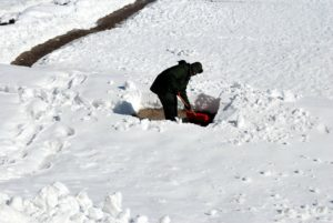 A man shoveling snow in the winter