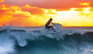 A man surfing during sunset.