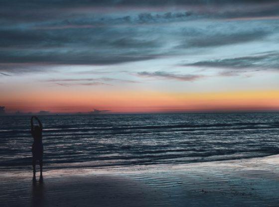 A woman stretching on a beach at dawn.