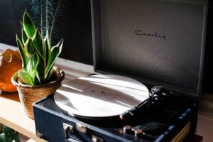 A potted plant next to a record player.