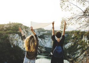 Two friends holding a flag while exploring the great outdoors, away from the urban jungle.