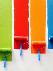 Four roller brushes in different colors, leaving a trace on a white wall.