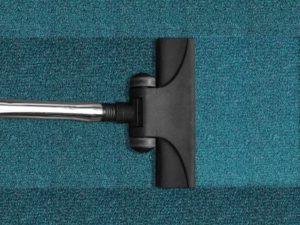 A vacuum cleaner used on a blue carpet, in order to make your new apartment feel like home.