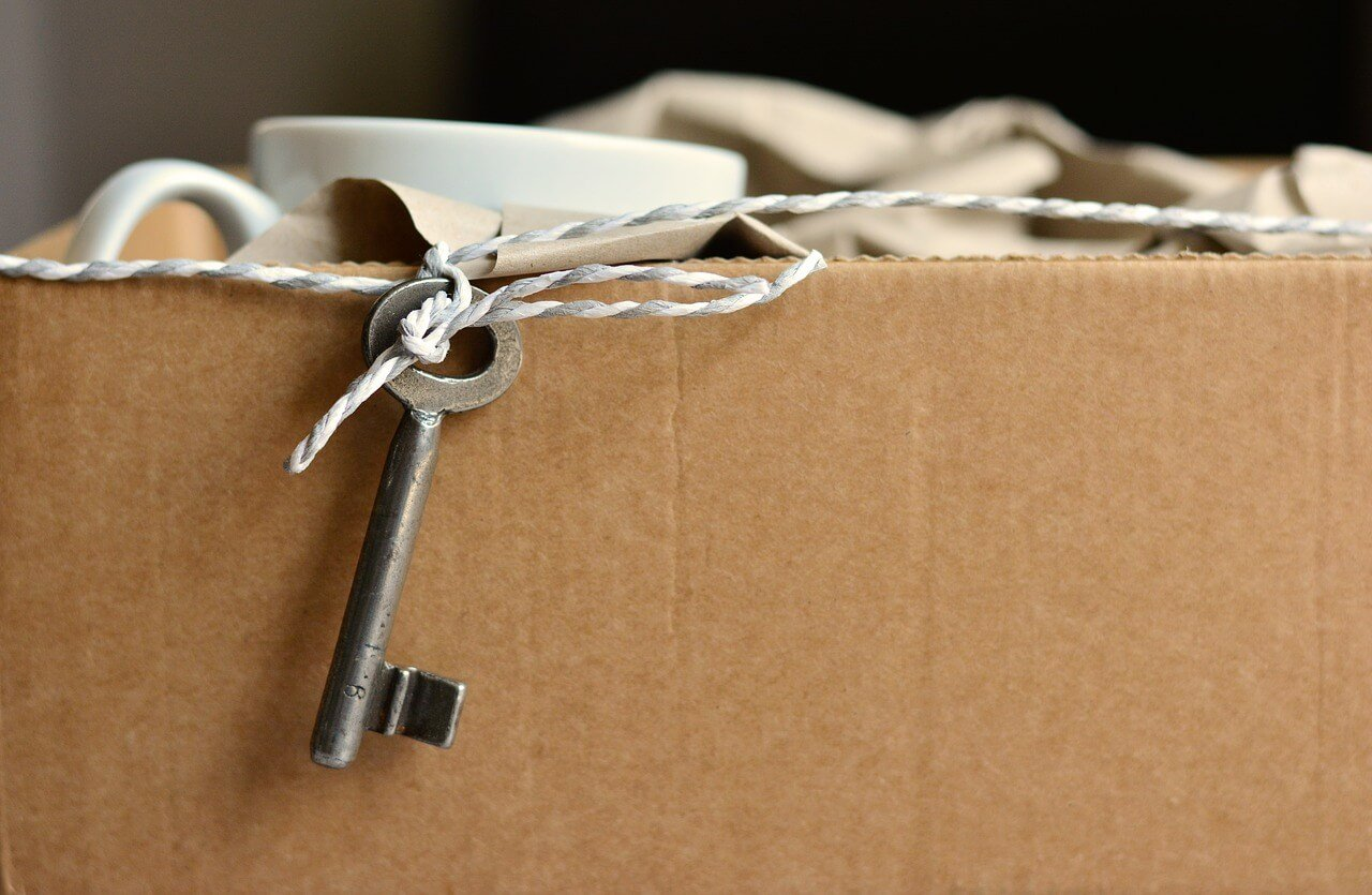 Cardboard box, keys and a cup