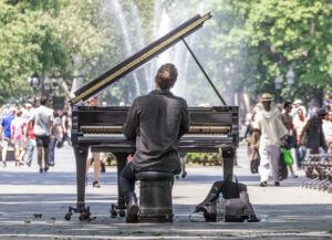 Man playing a piano in a park