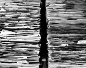 A stack of papers to be removed during office decluttering.