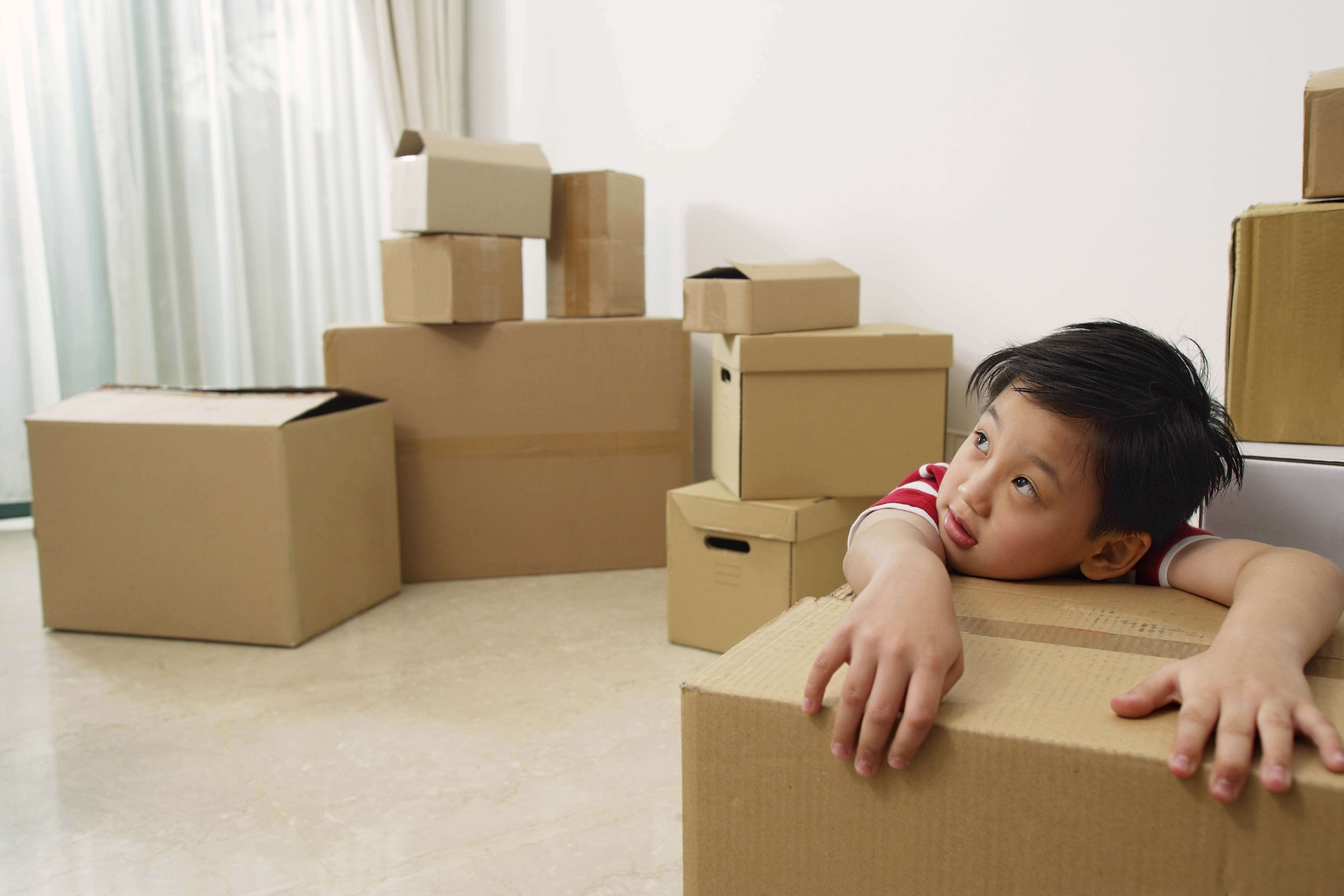 Boy surrounded by different types of moving boxes.