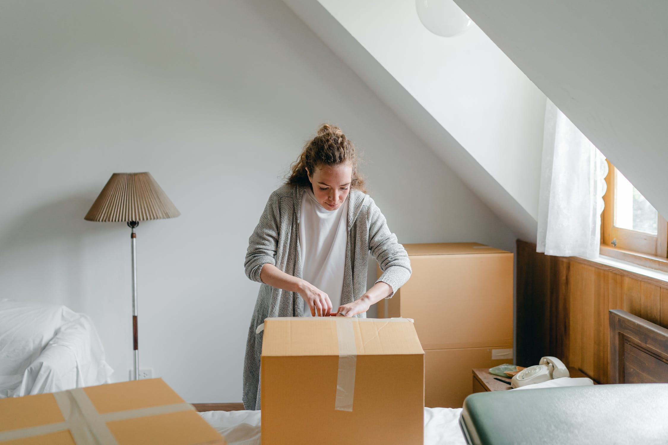 A woman packing for her move - moving from NoHo to SoHo is not easy, so be prepared for it