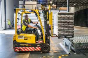 A worker driving a forklift
