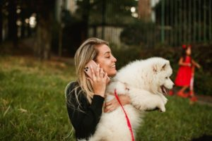 A girl talking on the phone while holding a dog