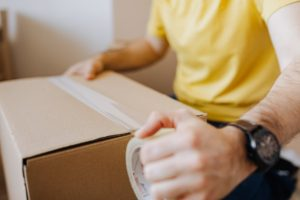 a man taping a cardboard box