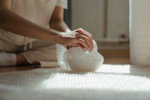 woman wrapping a ceramic bowl in bubble wrap