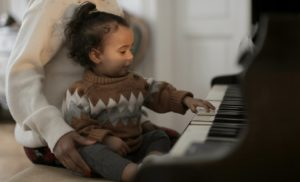 small girl playing a grand piano
