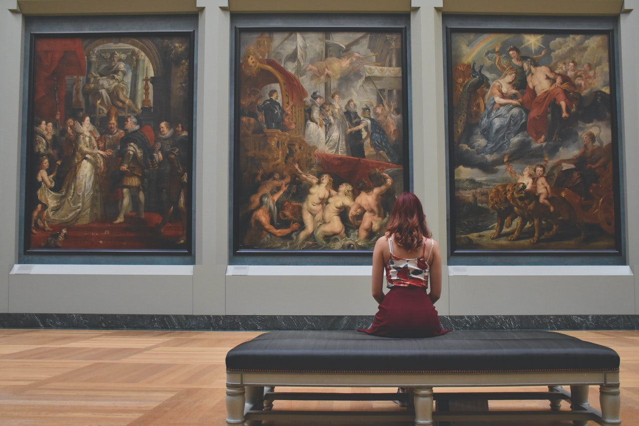 Girl looking at paintings and how to evaluate fine art movers to move them
