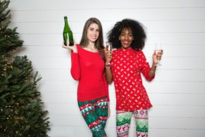 two women Celebrating New Year's Eve in Manhattan in pjs with champagne
