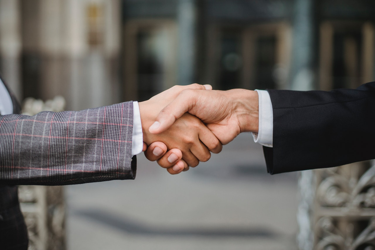 Two persons shaking hands while rent an apartment in Manhattan with a guarantor