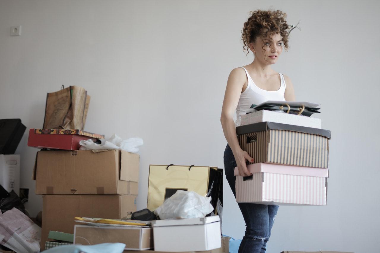 Girl holding boxes, beside her are more boxes and old stuff