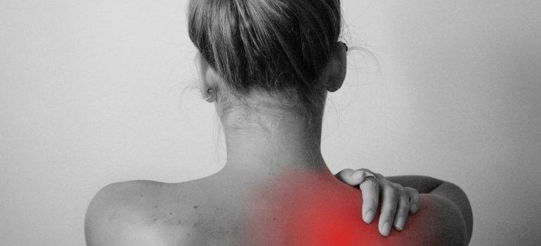girl from the back holding a shoulder/hiring professional packers for local moving help with a back pain