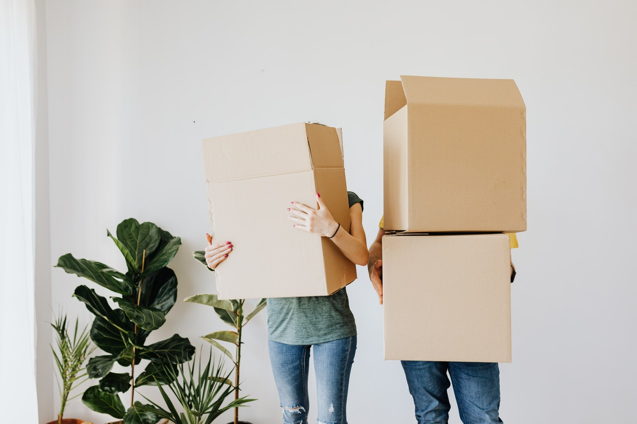Two people holding boxes in the way that you can't see their faces