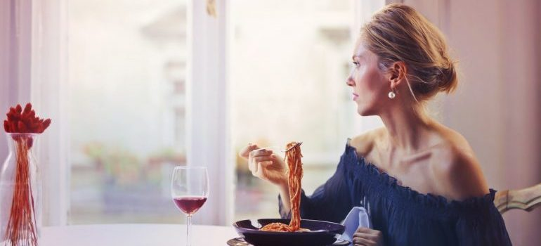 Woman sitting on chair while eating pasta dish in one of the most famous Manhattan neighborhoods